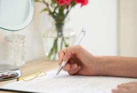 カウンセリングシートに記入する女性の手の写真
