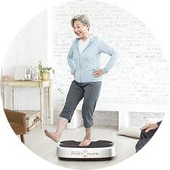 パーソナルパワープレートでトレーニングをする高齢女性の写真